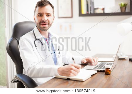 Friendly Young Doctor Working In His Office