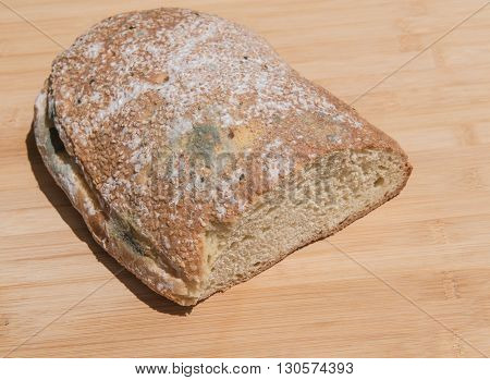 Piece of unhealthy homemade moldy bread on a wooden brown board.