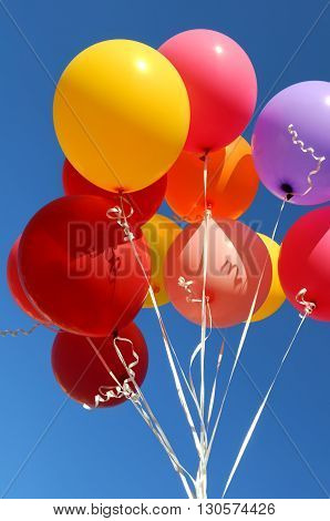 multicolored balloons in the city festival on blue sky background vertical composition