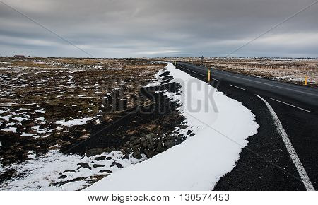 Rural empty straight road partly covered in snow in Reykjanes peninsula in Iceland