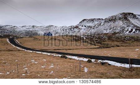 Typical Icelandic landscape at Reykjanes Peninsula with mountains covered in snow and empty asphalt road leading to a blue cottage house