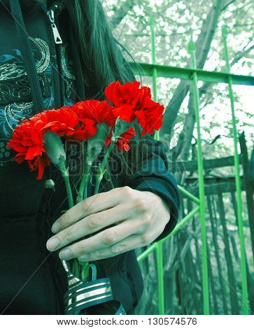 Red carnations with black gold ribbon in the hand