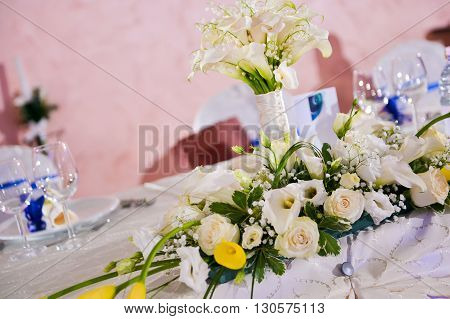 Bouquet of white callas and roses on a wedding table