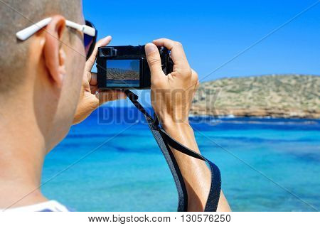 closeup of a young caucasian man seen from behind taking a picture of the Mediterranean sea and its coast in Ibiza Island, Spain, in the summer