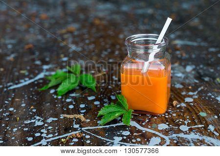 orange bottled carrot juice on wooden background