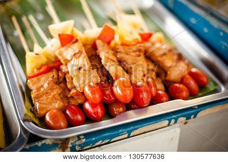 Fresh made pork satay skewer with pineapple red pepper aand tomatoe. Traditional thai cuisine on market.
