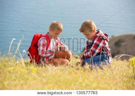 Two brothers walking in mountains near the sea