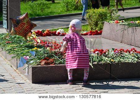 Zelenograd, Russia - May 09 2016: Little girl laying flowers at the monument to Marshal Rokossovsky in Victory Park