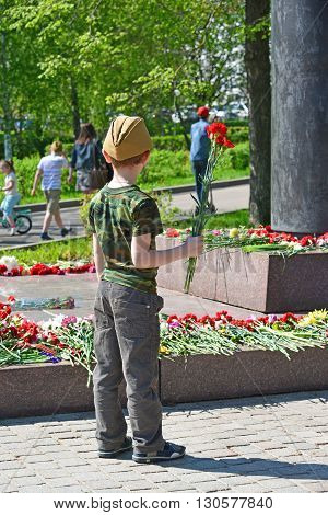 Zelenograd, Russia - May 09 .2016: Little boy laying flowers at the monument to Marshal Rokossovsky in Victory Park