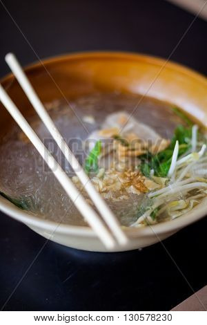 Fresh made thai glass noodle soup served with pork garlic and bean sprouts. Traditional thai cuisine.