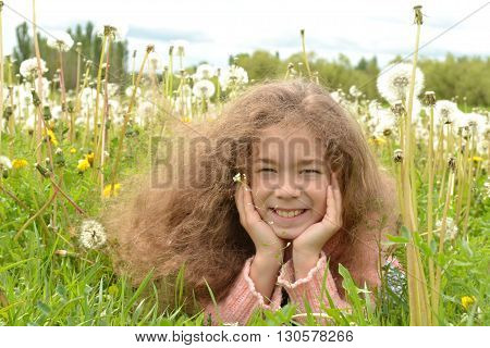 the beautiful girl's hair in the dandelions and she's having fun