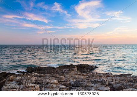 Rocky beach over skyline seacoast with beautiful sky background