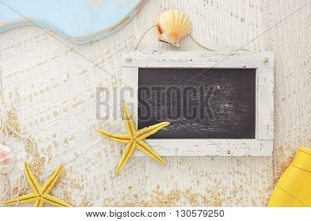 Holiday travel concept.  Empty blackboard, different marine items and suntan lotion on rustic background. Top view, vintage toned image, blank space