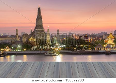 Opening wooden floor, Arun temple waterfront with dramatic sky background, Thailand landmark