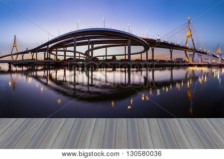 Opening wooden floor, panorama suspension bridge connect to highway and reflection night view