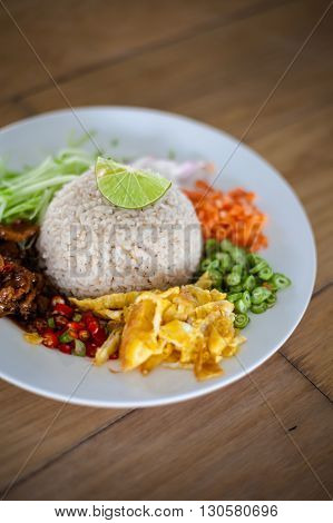 Rice with shrimps paste served with egg omelette bean carrot chilli papaya onion and sweet pork. Traditional thai cuisine.