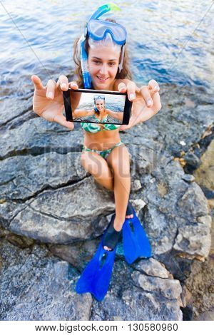 Girl in swimming suit and snorkeling gear taking a selfie with a smartphone on rock in Greece at the sea.