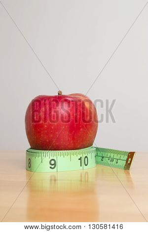 Apple on top of a measuring tape