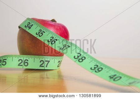 Measuring tape around an apple on wooden table