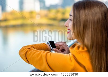 Young woman in yellow sweater using smart watch on the modern bridge with skyscrapers on the background. Sport application on the smart watch