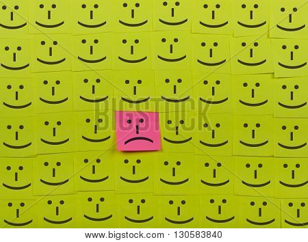 Unhappy and happy concept. Background of green sticky notes. Unhappy sticky note is among happy sticky notes.