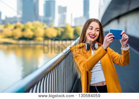 Young sport woman in yellow sweater making selfie photo with smart phone standing on the modern bridge with skyscrapers on the background.