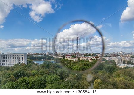 Romantic view of the TV tower in Minsk from ferris wheel in Gorky Park through a hole in the cabin