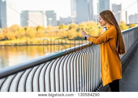 Young sport woman in yellow sweater using smart phone on the modern bridge with skyscrapers on the background.
