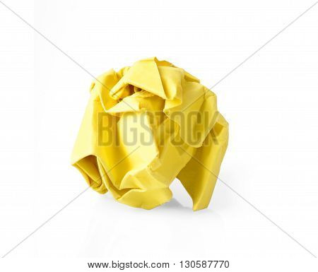 Yellow wrinkled paper ball isolated on white background symbol of recycling and wasting our resources.