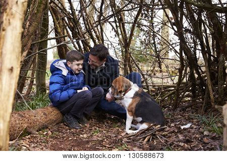 Father and son talking, under a shelter of branches with dog
