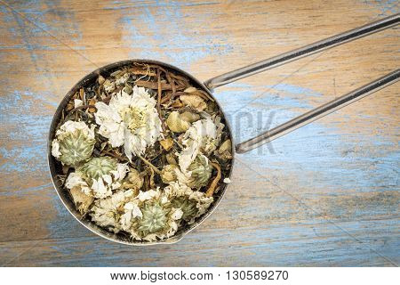 Scoop of cold, flu and cough herbal tea with chrysanthemum flower, chamomile, spearmint, ginger, honeysuckle