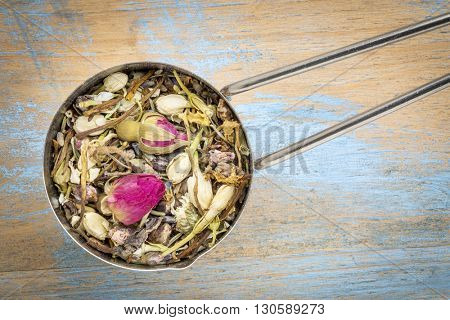 Measuring scoop of healthy skin herbal tea, a blend of  red rose bud. peach flower, lavender, rosemary, honeysuckle