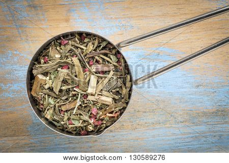 Measuring scoop of a Breathing and bronchitis herbal tea including ginkgo tea, lemon balm, lemon peel and green rooibos
