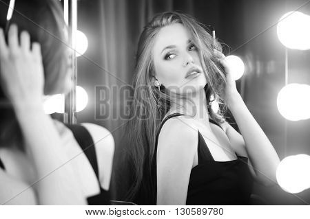 Beautiful caucasian woman looking into makeup mirror at herself and use cosmetic pencil. Black and white portrait.