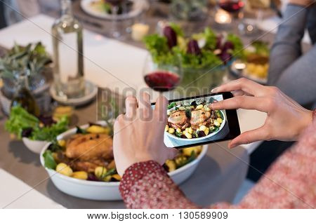 Close up of woman hands clicking picture of food. Woman using smartphone for food photography. Close up of female hands taking photo of roasted chiken with smart phone.