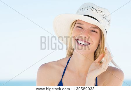 Portrait of smiling  woman on beach wearing blue bikini and straw hat. Close up face of beautiful young woman feeling good at seaside. Happy girl wearing sun hat and looking at camera.