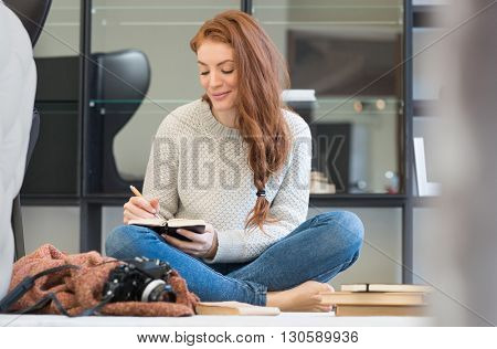 Happy young woman writing in diary. Young woman booking her dates in diary. Happy young photographer writing in her personal organizer.