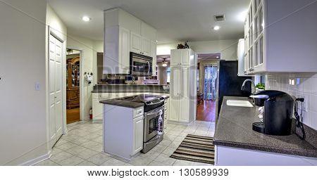 panoramic shot of dated white kitchen
