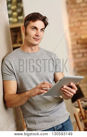 Casual man holding tablet computer, thinking, looking away.