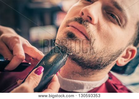 Female barber shaving a client's beard with trimmer in a barber shop. Close-up