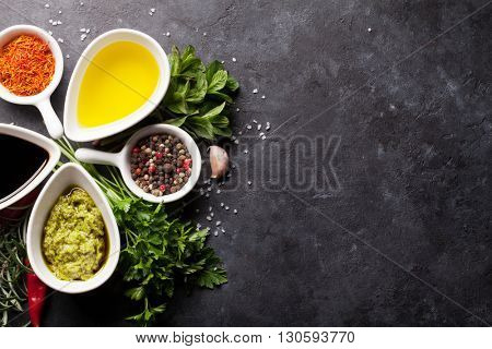 Herbs, condiments and spices on stone background. Top view with copy space