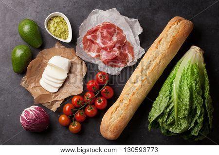Ciabatta sandwich cooking with romaine salad, prosciutto and mozzarella cheese over stone background. Top view