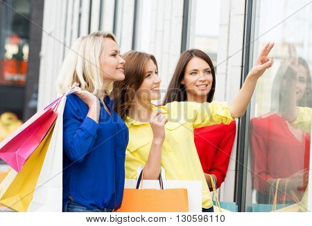Three beautiful young female shopaholics checking the dress out in store window.