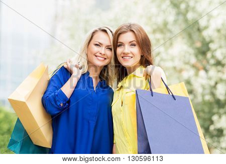 Portrait of two attractive happy women being outside in the park with shopping bags.
