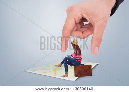 Hipster woman sitting on her suitcase against city map