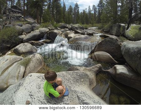 Young boy sitting on boulder next to waterfall in Yosemite wilderness.