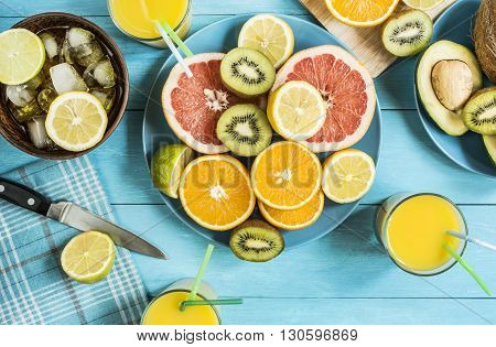 Citrus fruit juice ice knife on a blue wooden table top view