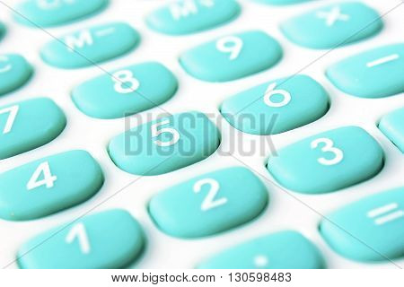 Calculator with turquoise color buttons close up