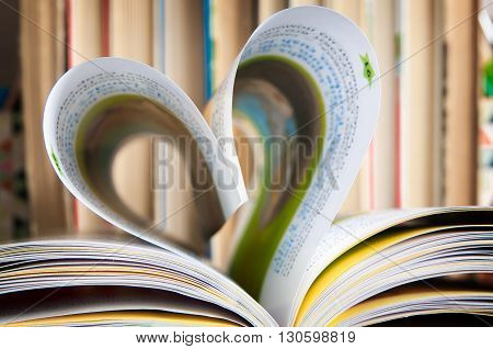 Paper pages of a book folded in the form of heart on the background of a series of old books