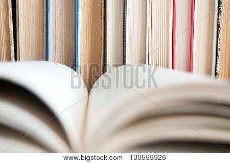 Paper pages of a book folded on the background of a series of old books